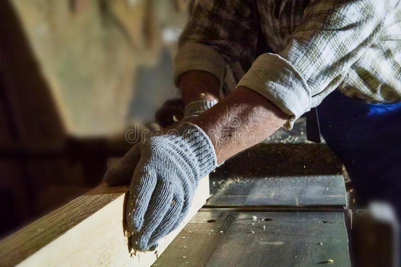 Le charpentier travaille aux machines de travail du bois dans l'atelier de menuiserie photos stock