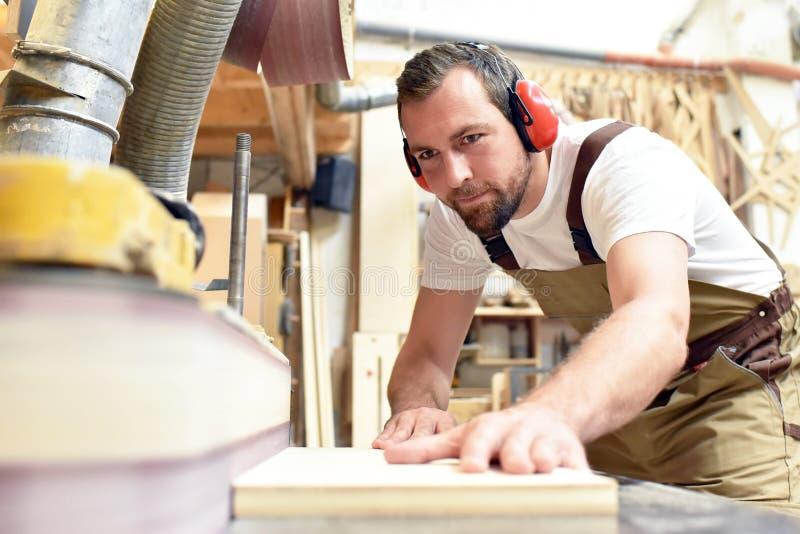 Le charpentier travaille en menuiserie - atelier pour le travail du bois et le sawi photographie stock
