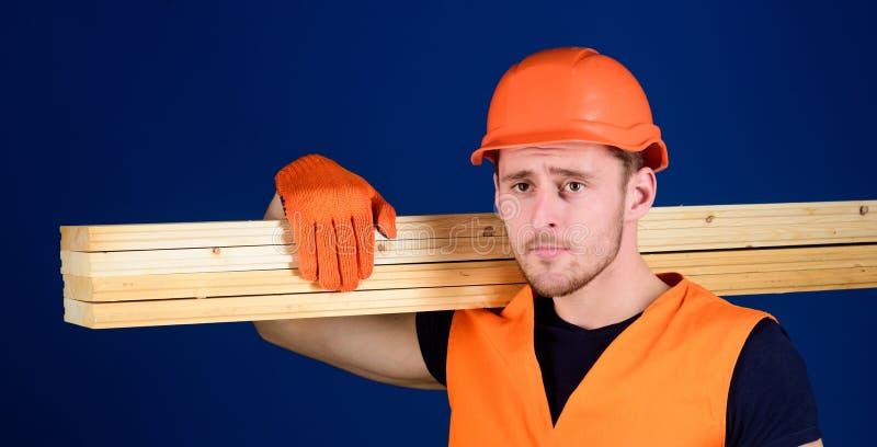 Le charpentier, travailleur du bois, constructeur fort sur le visage réfléchi porte le faisceau en bois sur l'épaule Homme dans l images stock