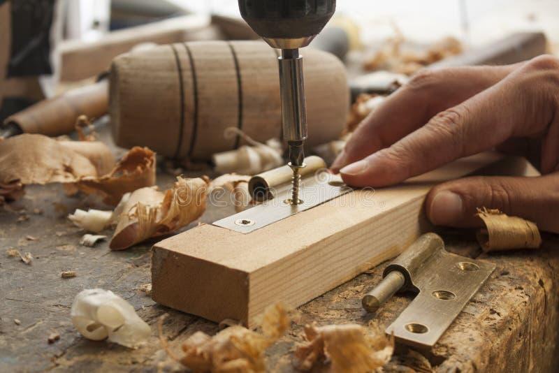 Le charpentier a vissé une charnière photos libres de droits