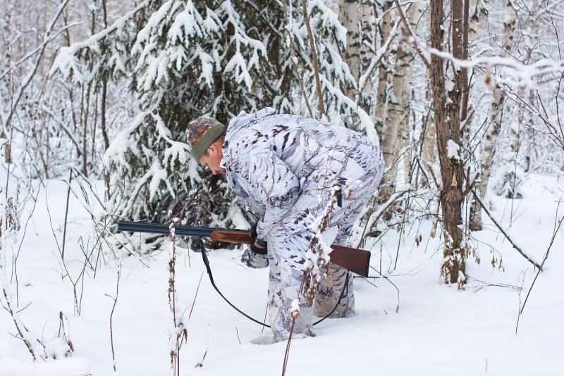 Le chasseur examine la traînée de l'animal photo stock