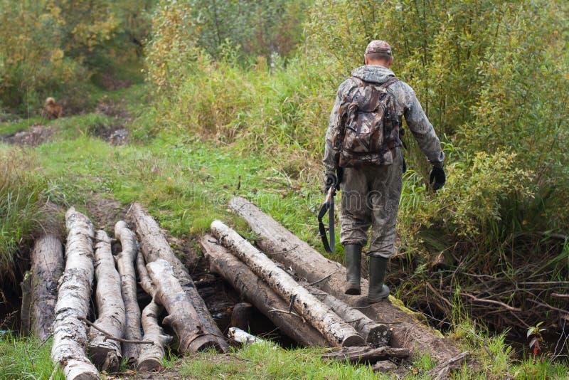 Le chasseur a traversé la rivière de forêt sur le pont images stock