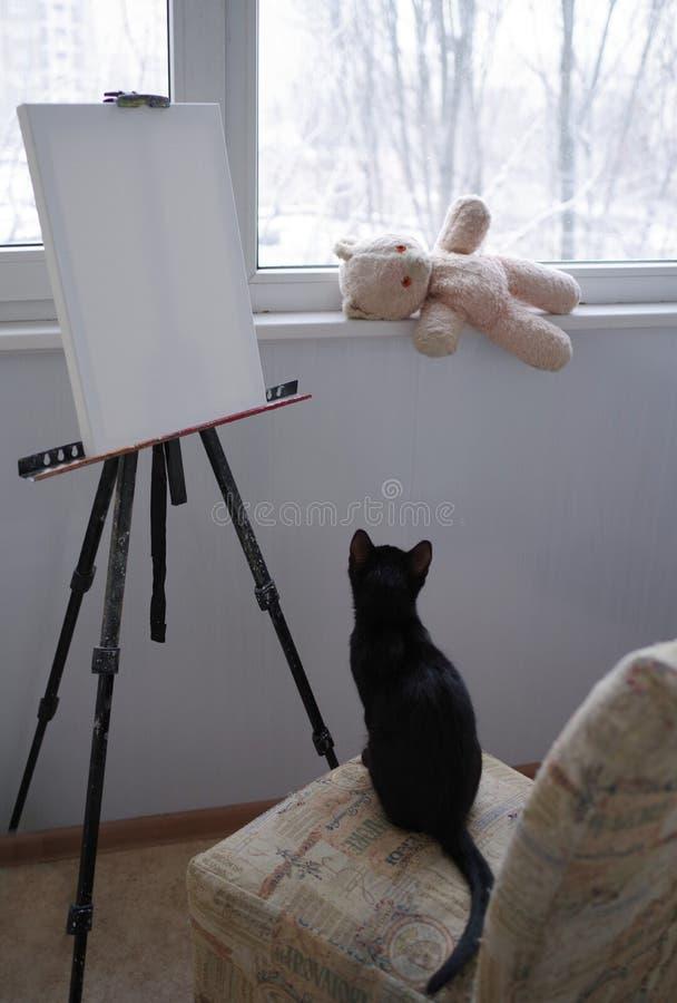 Le chat noir se repose sur une chaise devant le chevalet avec une toile vide et regarde un ours de nounours Hiver en dehors de la photographie stock libre de droits