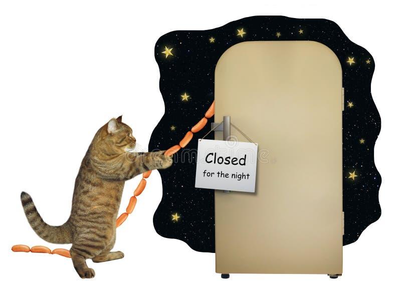 Le chat vole la saucisse du réfrigérateur photo stock