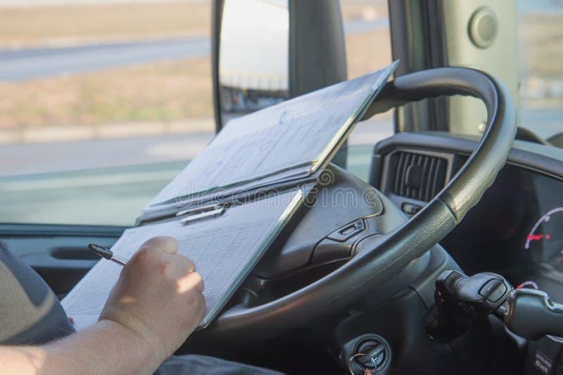 Le chauffeur de camion écrit dans la documentation photographie stock