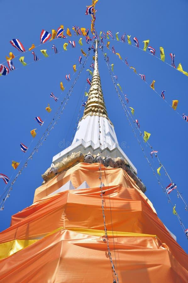 Le chedi en pierre drapé dans le tissu orange monte dans le ciel bleu photographie stock libre de droits