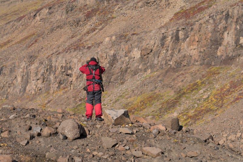 Le chef armé d'expédition fixe le terrain au Groenland images stock