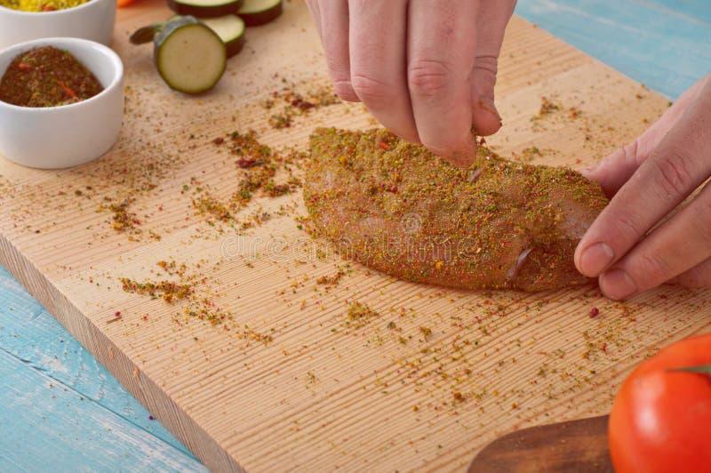 Le chef arrose le blanc de poulet épicé d'épices image stock