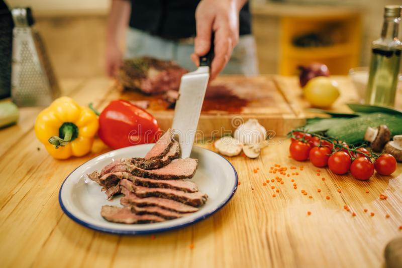 Le chef avec le couteau met la viande r?tie dans le plat photos libres de droits