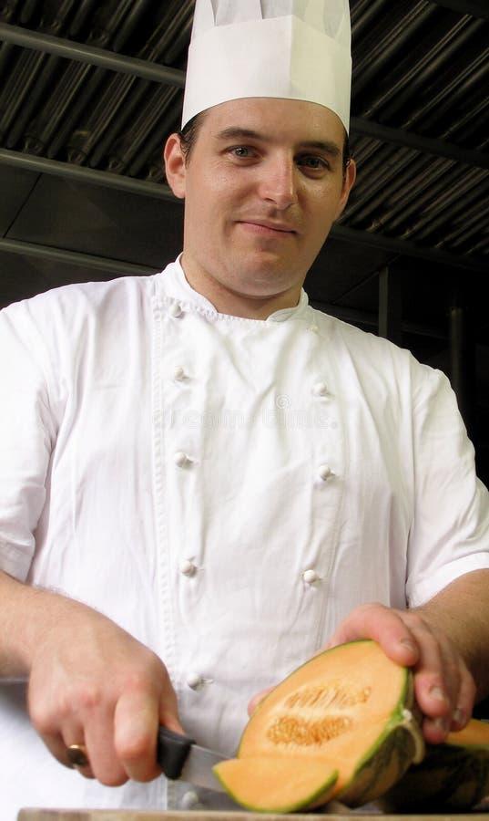 Le chef coupe en tranches un melon images libres de droits