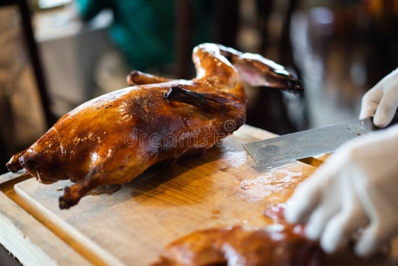 Le chef coupe la peau de canard du canard de Pékin avec un couteau très pointu à un restaurant chinois célèbre images libres de droits