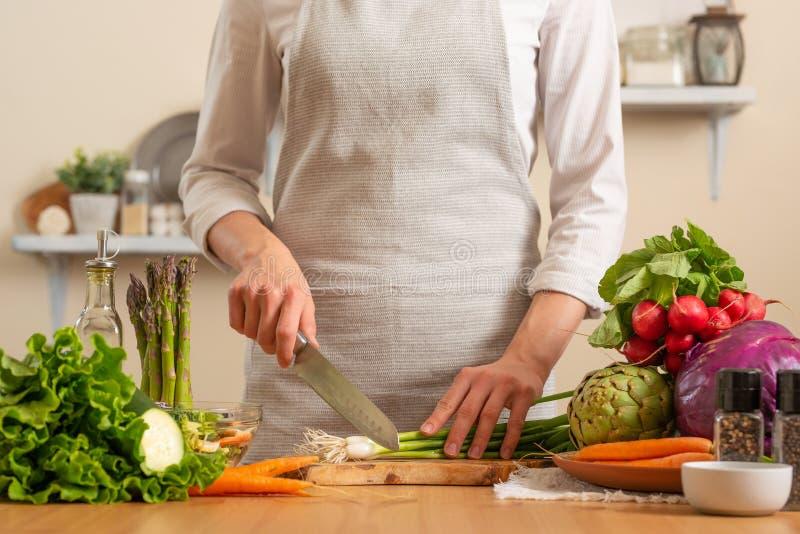 Le chef coupe les oignons verts, sur un fond clair Le concept de la nourriture saine et saine de perte, detox, végétariens, régim image libre de droits