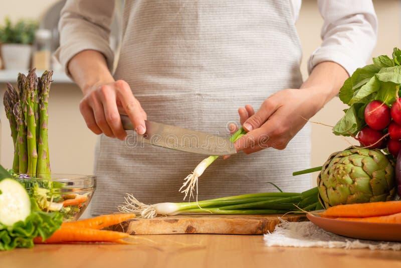 Le chef coupe les oignons verts, sur un fond clair Le concept de la nourriture saine et saine de perte, detox, végétariens, régim images stock