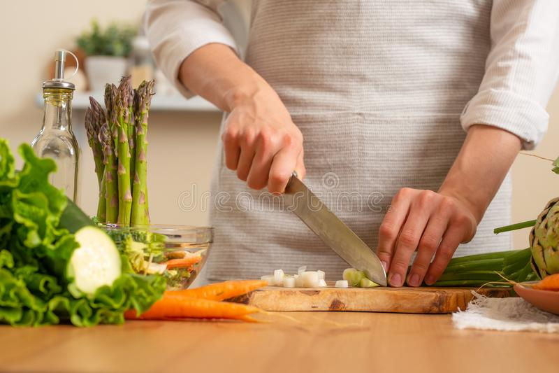 Le chef coupe les oignons verts, sur un fond clair Le concept de la nourriture saine et saine de perte, detox, végétariens, régim photo stock