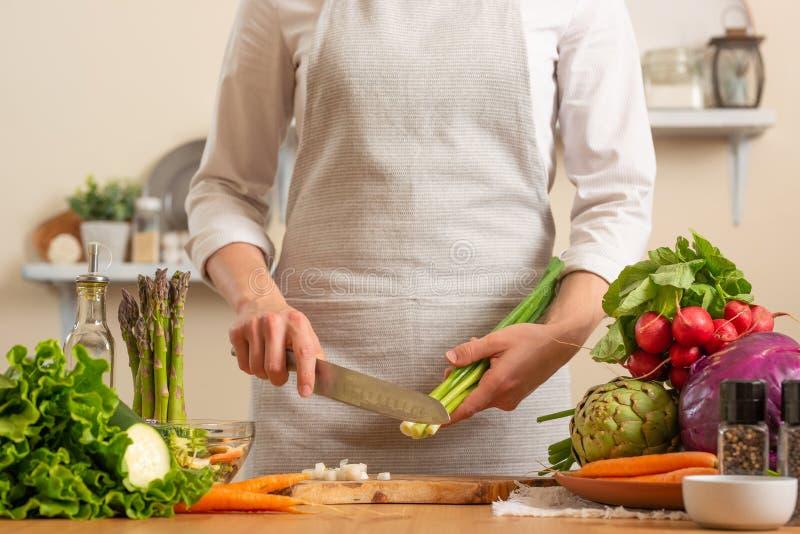 Le chef coupe les oignons verts, sur un fond clair Le concept de la nourriture saine et saine de perte, detox, végétariens, régim image stock