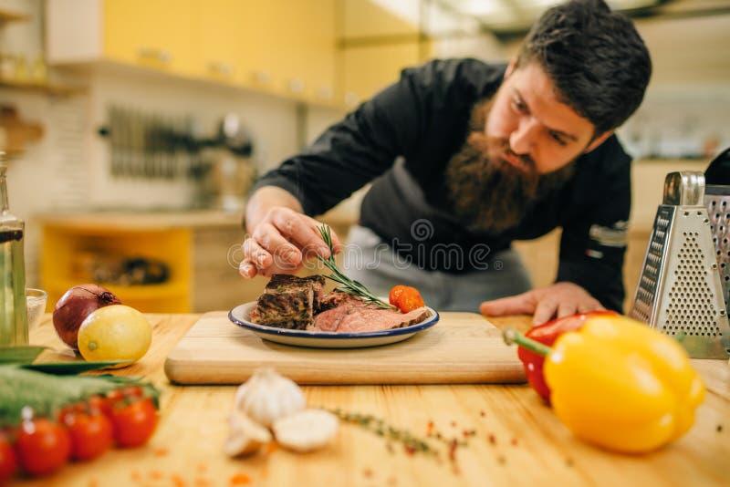 Le chef d?core les tranches de viande r?ties par herbes dans le plat photographie stock