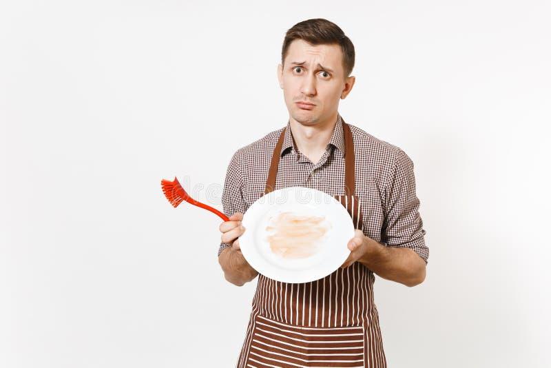 Le chef d'homme d'amusement dans le tablier brun rayé, chemise juge des lavages blancs autour du plat sale vide avec la brosse ro images libres de droits