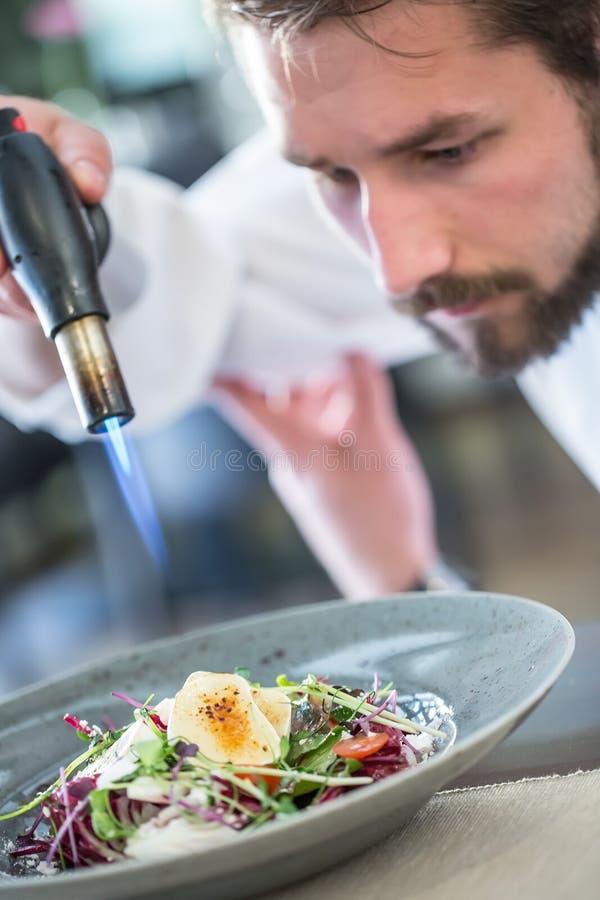 Le chef dans la cuisine d'hôtel ou de restaurant grille le fromage de chèvre images libres de droits