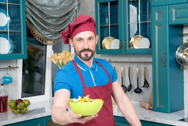 Le chef dans le polo bleu et le tablier tient le plat vert avec de la salade Le cuisinier barbu beau dans le chapeau aime faire c images libres de droits