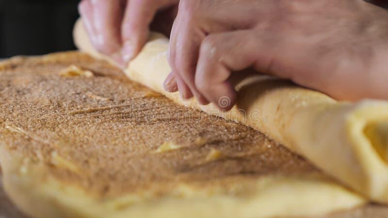Le chef de Baker roule la p?te avec de la cannelle, le sucre et le beurre dans un petit pain sur la table photos stock