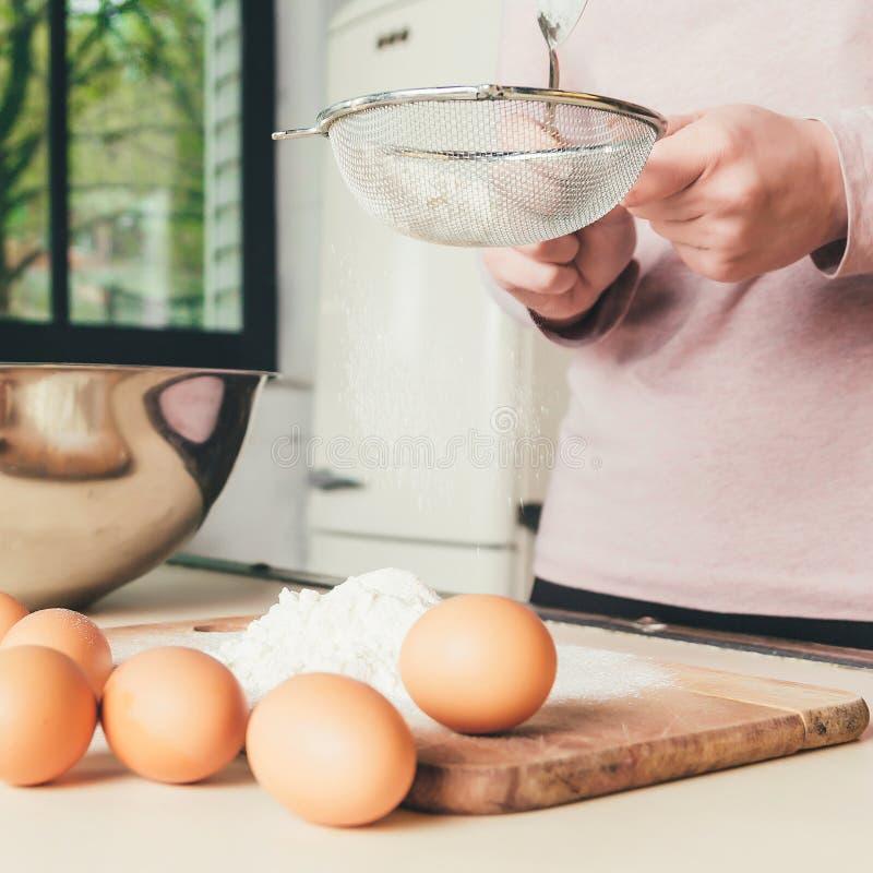 Le chef de femme tamise la farine, malaxent la pâte Boulangerie ou concept de cuisson Ingrédients pour la pâte images libres de droits