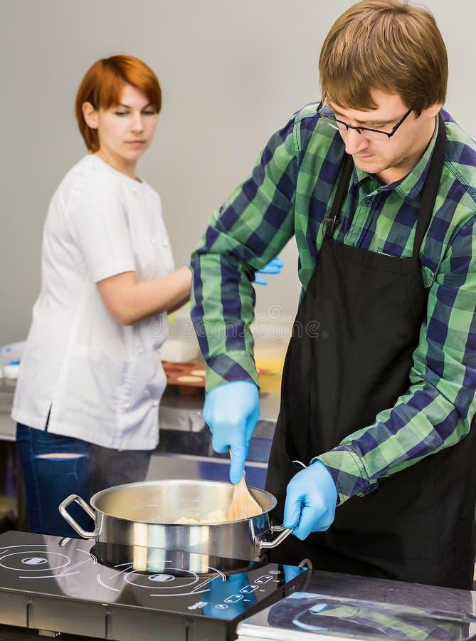Le chef de pâtisserie brasse la pâte Elle l'aide à faire cuire dans la cuisine photos stock