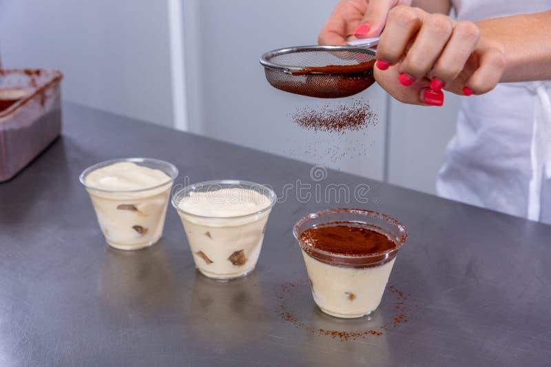 Le chef de pâtisserie dans la cuisine fait le tiramisu avec des framboises Le cuisinier arrose le cacao sur un dessert disposé da photo libre de droits