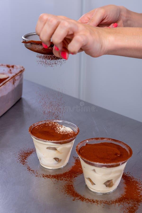 Le chef de pâtisserie dans la cuisine fait le tiramisu avec des framboises Le cuisinier arrose le cacao sur un dessert disposé da photos stock