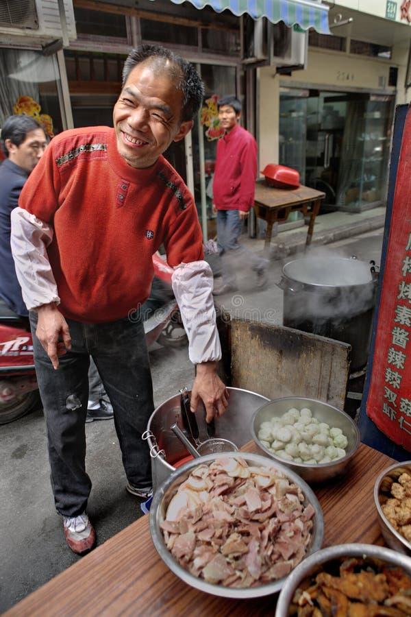 Le chef de sourire de rue vend la nourriture chaude sur un morceau étroit image libre de droits