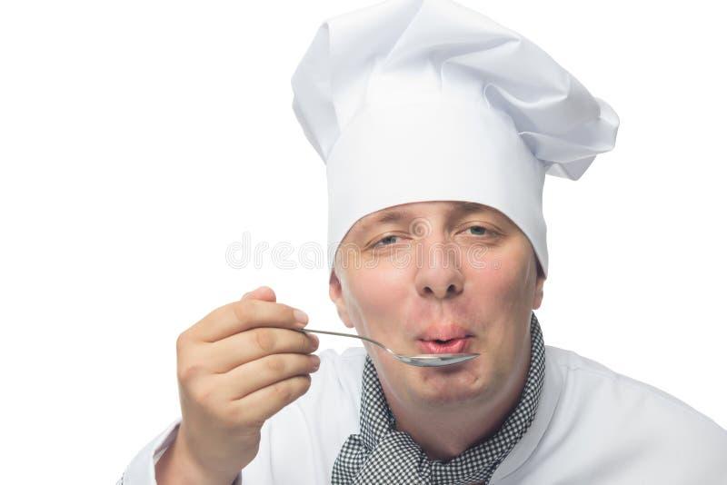 Le chef essaye son plat sur un fond blanc photo libre de droits