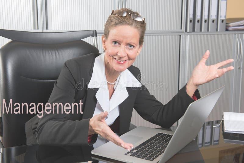 Le chef féminin dans le bureau aime des résultats - souriant photographie stock