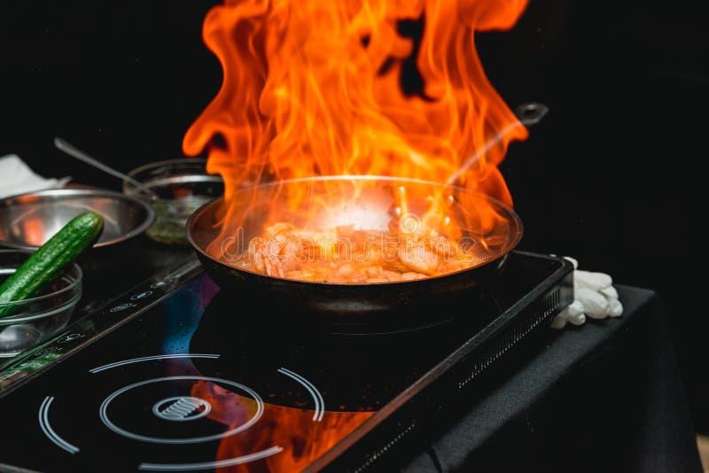 Le chef fait cuire la crevette sur une poêle en métal images stock
