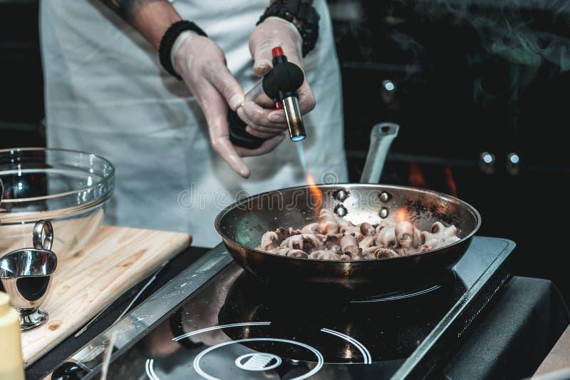 Le chef fait cuire le petit poulpe sur une poêle en métal images libres de droits
