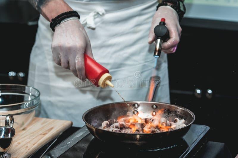 Le chef fait cuire le petit poulpe sur une poêle en métal photo stock