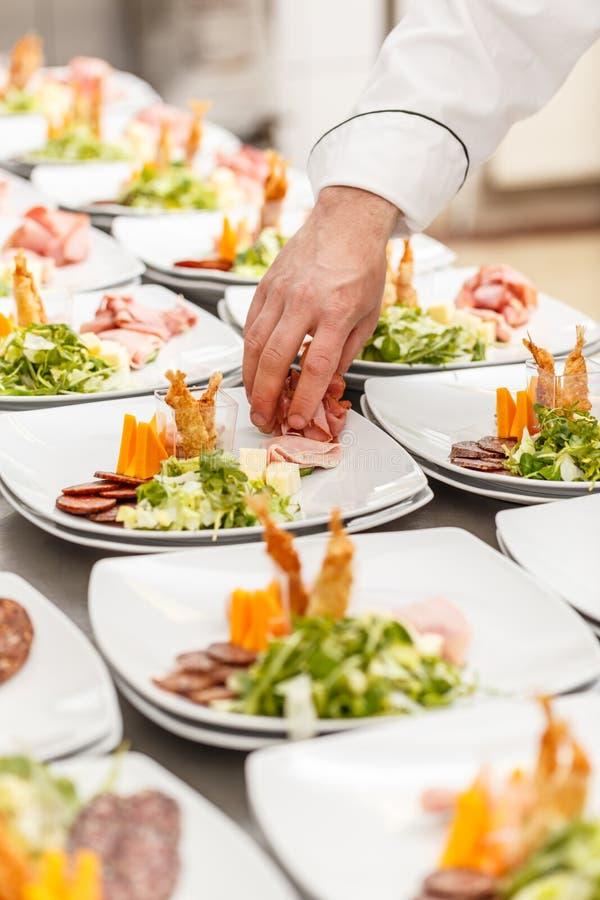 Le chef garnit les plats délicieux d'apéritif images libres de droits