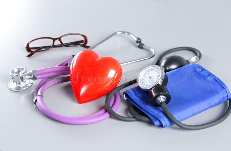 Le chef médical de stéthoscope et le coeur rouge de jouet se trouvant sur le cardiogramme dressent une carte le plan rapproché ai images libres de droits