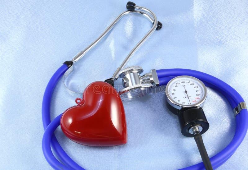 Le chef médical de stéthoscope et le coeur rouge de jouet se trouvant sur le cardiogramme dressent une carte le plan rapproché ai images stock