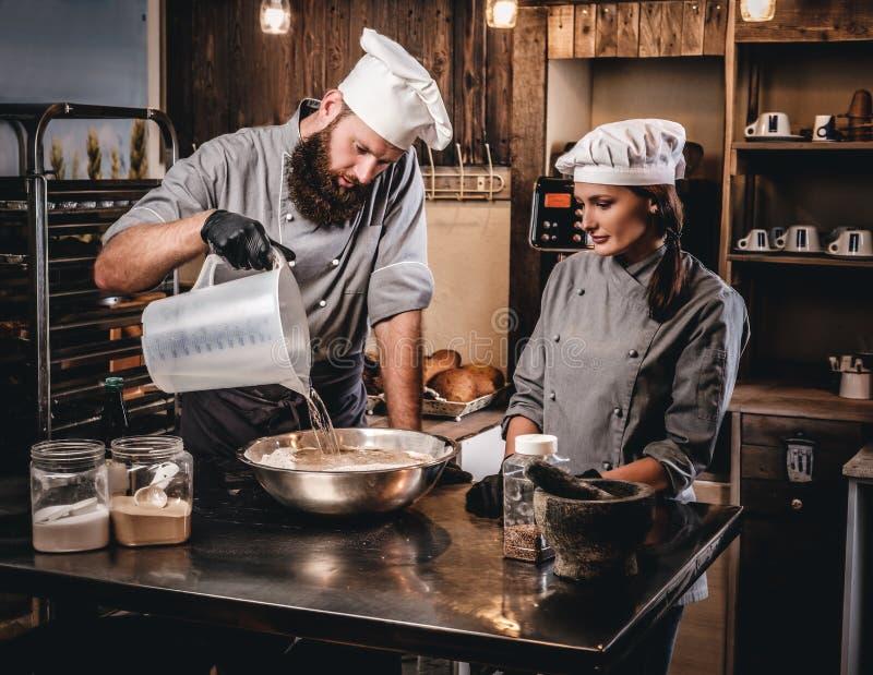 Le chef mélange les ingrédients pour la pâte Chef enseignant son assistant à faire le pain cuire au four dans la boulangerie photo libre de droits