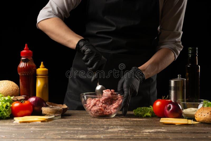 Le chef m?lange le boeuf hach? frais, pour cr?er un petit p?t? d'hamburger Sur le fond avec des ingr Gastronomie, photographie stock