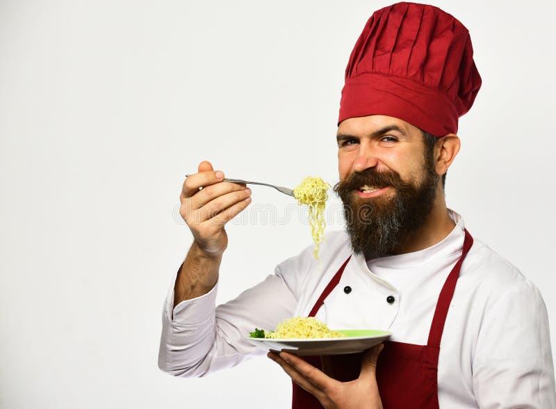 Le chef mange les nouilles italiennes ou asiatiques Homme avec la barbe image stock