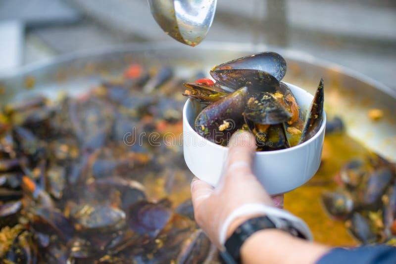 Le chef met des moules Beau déjeuner ou dîner Nourriture saine vivante Plan rapproché d'un plongeur dans sa main et un plat des m images stock