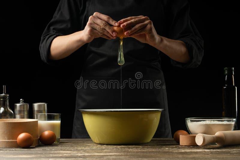 Le chef prépare la pâte pour le pain, la pizza et les bonbons Le concept de la nourriture Sur un fond noir, gelant dans le mouvem image stock