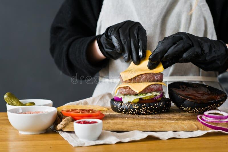 Le chef prépare un hamburger énorme Le concept de faire cuire le cheeseburger noir Recette faite maison d'hamburger images stock