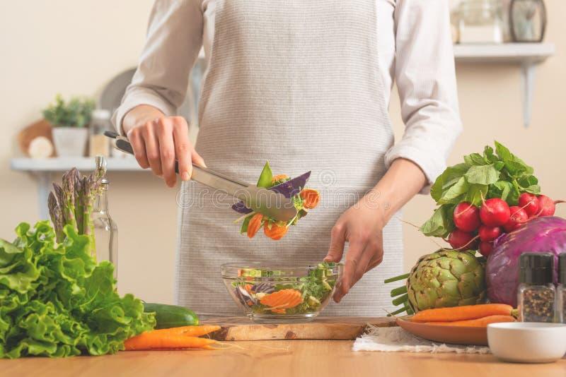 Le chef prépare une salade fraîche et lumineuse, avec des légumes sur un fond clair Le concept de la nourriture saine et saine de photo stock