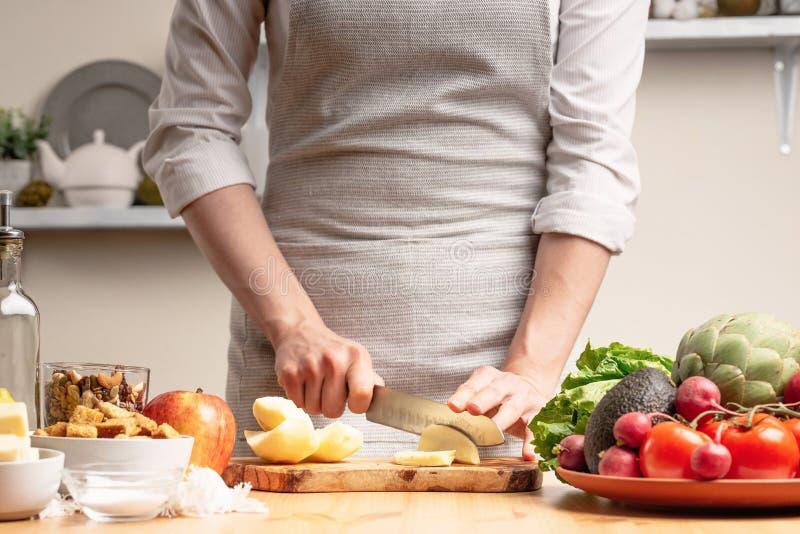 Le chef prépare une salade végétarienne avec la main d'un chef dans la cuisine à la maison Fond clair avec le secteur des textes  images libres de droits