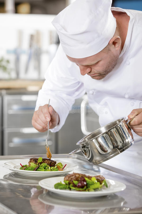 Le chef professionnel focalisé préparent le plat de viande au restaurant images libres de droits