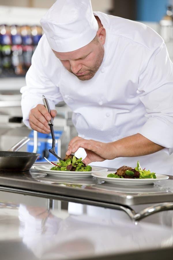 Le chef professionnel préparent le plat de bifteck au restaurant image stock