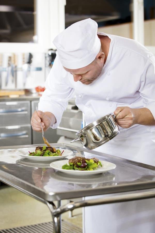 Le chef professionnel préparent le plat de viande au restaurant image stock