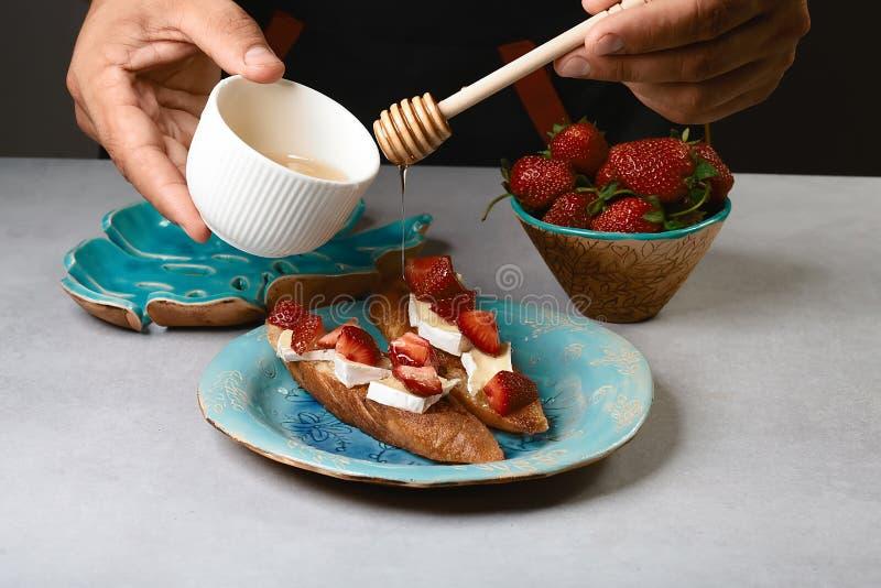 Le chef que le cuisinier prépare la bruschette italienne verse le miel avec des fraises, fromage, camembert, brie, faisant cuire  image libre de droits