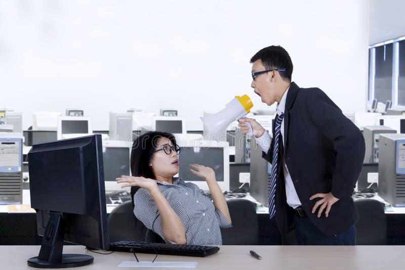 Le chef réprimande son employé avec le mégaphone photo libre de droits